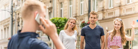 Group of friends stumbling across their mate who is talking on the phone Stock Photo