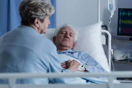 Wife sitting on a hospital bed by an elder man in a coma Stock Photo