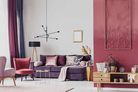 Red armchair next to a purple settee in cozy living room interior with wooden cupboard and lamp Stock fotó