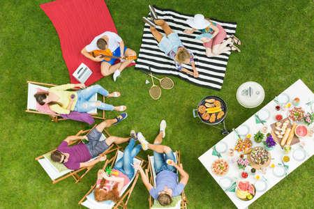 Vista superior del grupo de jóvenes amigos que tienen fiesta de barbacoa de verano en el patio trasero con parrilla y mesa llena de deliciosa comida Foto de archivo