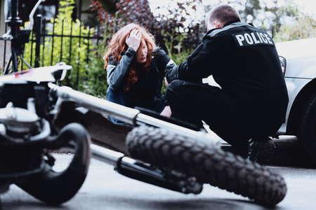 衝突後にバイクのぼんやりした運転手にインタビューする警官