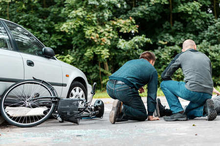 Witnesses of a road collision between a car and a bicycle helping a victim