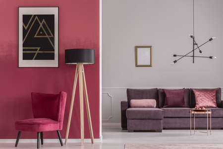 Black poster on red wall above armchair and wooden lamp in open space interior with mockup Stock Photo