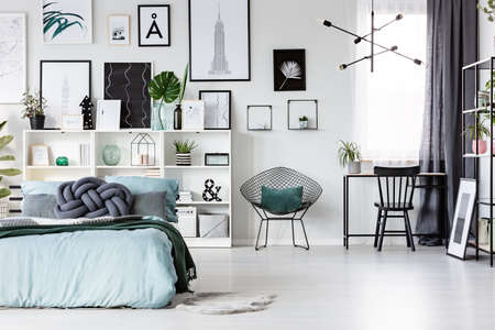 Freelancer's bedroom interior with blue bed and black, wooden chair at a desk near the window Stok Fotoğraf