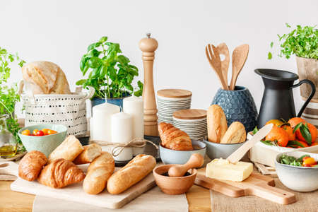 Home breakfast buffet table with wooden kitchen utensils and fresh food - bread, butter and herbs