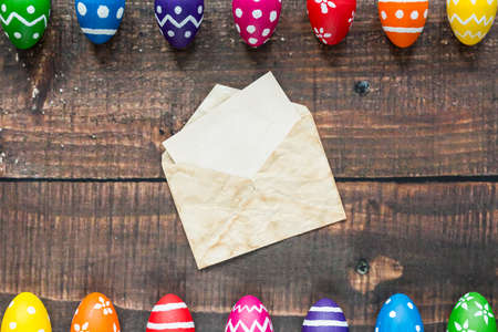 Colorful painted eggs and letter in envelope on the wooden table