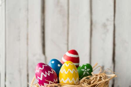イースターのために準備された巣の中でかわいいカラフルな塗られた卵 写真素材