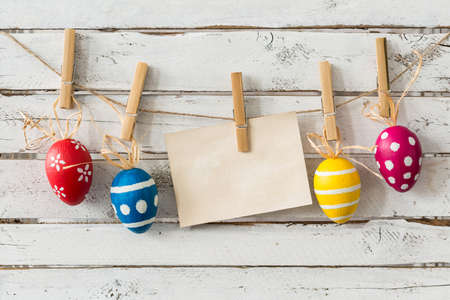 Colorful eggs hanging on a lace with clothes pin Stock Photo