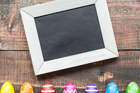 塗装卵の横の白いフレームの黒い紙 写真素材