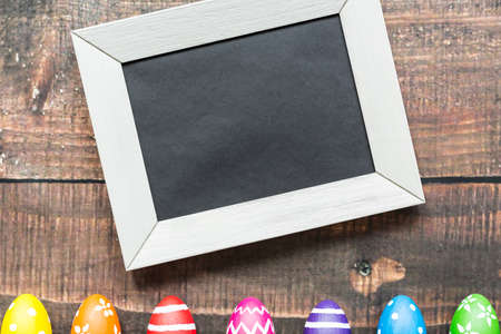 Piece of black paper in white frame next to painted eggs