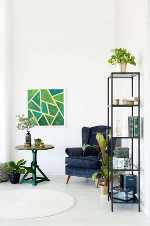 Modern living room interior with emerald armchair, white rug, bookcase, table with table set, green poster and plants Zdjęcie Seryjne - 97824834