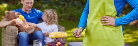 Mum preparing corn on the grill for hungry father and son in the park
