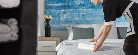 Panorama of maidservant arranging towels on a bed according to hotel standards