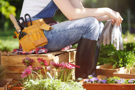 Close-up of professional gardener in jeans and wellies sitting on a wooden crate