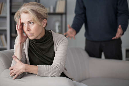 Sad wife looking ahead, sitting on a sofa in a room with her angry husband behind her Stock Photo