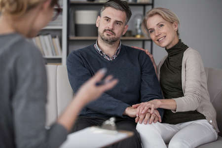 Young marriage during marital therapy smiling to their blond therapist in glasses
