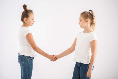 Blonde girls shaking hands after a fight, standing against white background