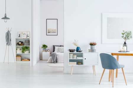 Grey chair at wooden table in white open space interior with poster on the wall and bright bedroom Stok Fotoğraf - 97824810