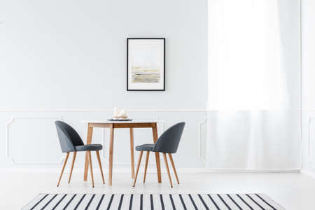 Grey chairs at wooden table in minimalist white dining room interior with poster and window Stockfoto