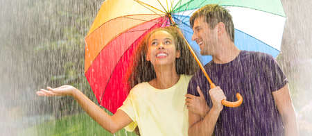 Multicultural young couple under rainbow umbrella during rainy stroll in the park