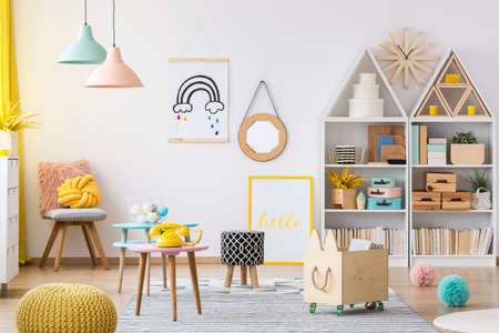 Wooden crate and yellow pouf in colorful kids playroom interior with poster and patterned stool