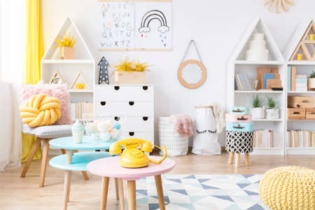 Stock Photo   Yellow Phone On Pink, Round Table In Scandi Childu0027s Playroom  Interior With Poster On The Wall