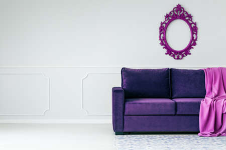 Violet mirror above purple sofa with blanket in living room interior with copy space on grey wall
