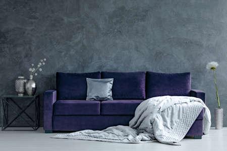 Manta gris en el sofá violeta junto a la mesa con jarrones plateados en el interior de la sala de estar con muro de hormigón Foto de archivo