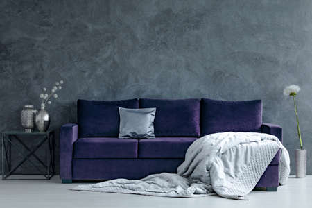Grey blanket on violet couch next to table with silver vases in living room interior with concrete wall