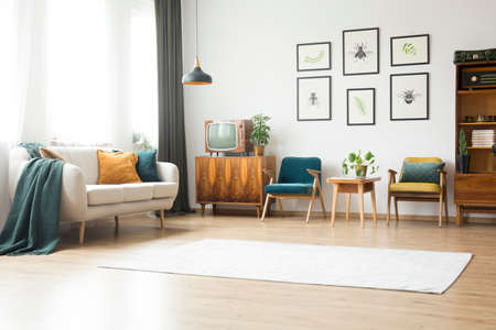Beige Couch, Vintage Armchairs And Wooden Cupboard With Old Fashioned Tv In  Bright Living