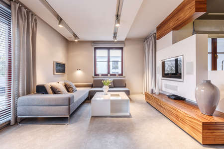 Big, gray corner sofa standing on beige marble floor of a bright, luxurious living room interior with elegant, white coffee table