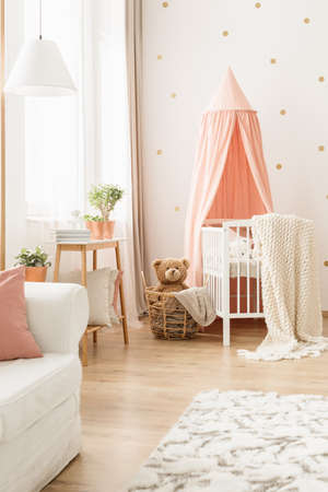 Cozy blanket on a white, modern baby crib with a pink canopy and a teddy bear in a wicker basket in a nursery room interior Banco de Imagens