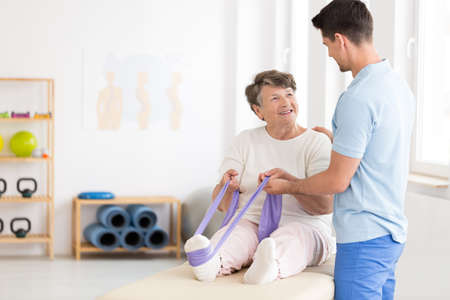Elderly woman exercising her leg with a stretch band with assistance of a young physiotherapist Standard-Bild