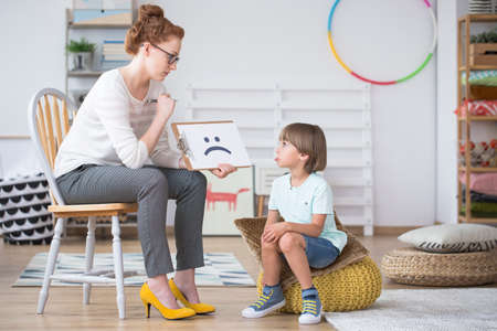 Psychologist sitting on a chair and showing a drawing of a sad face to a boy
