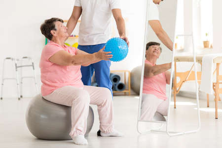 Physiotherapist helping a senior woman sitting on an exercise ball maintain posture and coordination Stock Photo