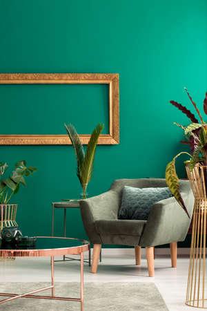 Moderne fauteuil en een gezellig kussen in een luxueus, groen, botanisch woonkamerinterieur met gouden meubels en decoraties