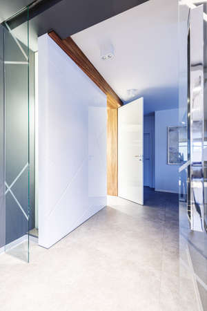 White, spacious hallway of a luxurious, modern interior with hidden door, wooden and glass elements and beige marble floor