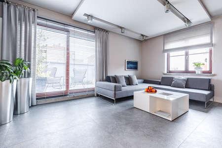 Intérieur de salon lumineux, moderne et spacieux avec des meubles gris, des murs beiges et de la lumière provenant de grandes fenêtres avec accès au balcon