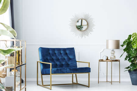 Navy blue armchair next to gold table with lamp against white wall with mirror in living room interior 版權商用圖片