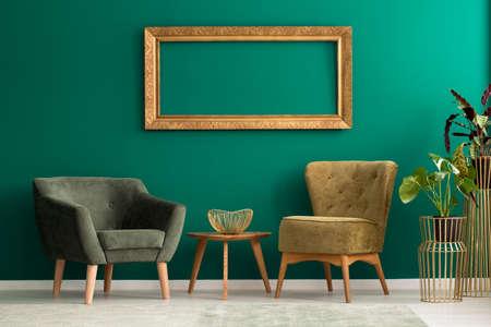 Cadre vide au-dessus de chaises rembourrées rétro dans un salon vert avec des plantes et des décorations dorées Banque d'images