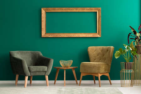 Empty frame above retro, upholstered chairs in a green living room interior with plants and golden decorations