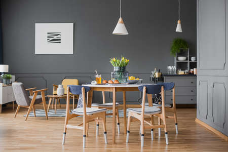 A wooden table and chairs in grey dining room interior with black walls