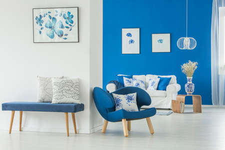An armchair, bench, sofa and paintings in white and blue themed living room interior Stok Fotoğraf - 98101335