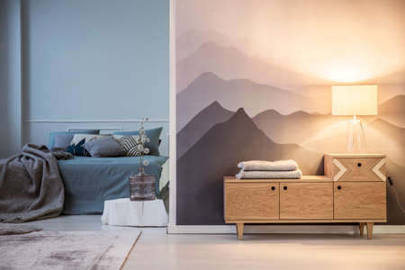 Double bed with blue and gray bedding and a table lamp on a wooden cabinet by mountains wallpaper illuminating a cozy bedroom interior