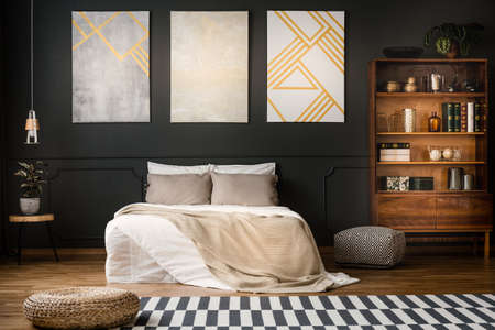 Elegant, wooden, antique bookcase in a dark, modern bedroom interior with a black wall and beige paintings with golden elements Stockfoto