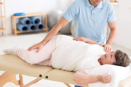 Chiropractor performing back bones adjustment on a senior woman lying on a table in rehabilitation Фото со стока