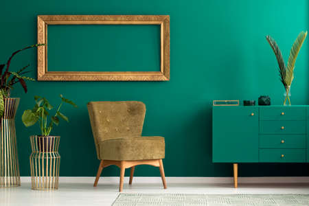 Palm leaf on a modern, teal sideboard with drawers in a luxurious, green living room interior with golden decorations and an upholstered chair Stockfoto
