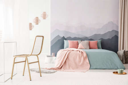 Gold, metal chair in a soft, bright bedroom interior with a mountains wallpaper, pastel pink and blue bedding and pillows Stockfoto
