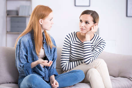 Teenage girl and a woman sitting on a gray couch and talking about problems in a bright, modern living room interior