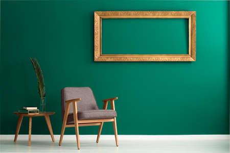 Leerer goldener Rahmen auf einer grünen Wand, einem Palmeblatt in einem Vase auf einem hölzernen Beistelltisch und einem Lehnsessel in einem Wohnzimmerinnenraum